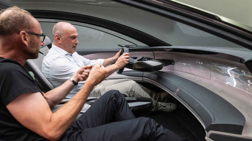 Das Lenkrad verschwindet auf Wunsch komplett  Designchef Marc Lichte und Autor Wolfgang Gomoll bei der Sitzprobe im Konzeptauto Grandsphere von Audi. Foto: Audi