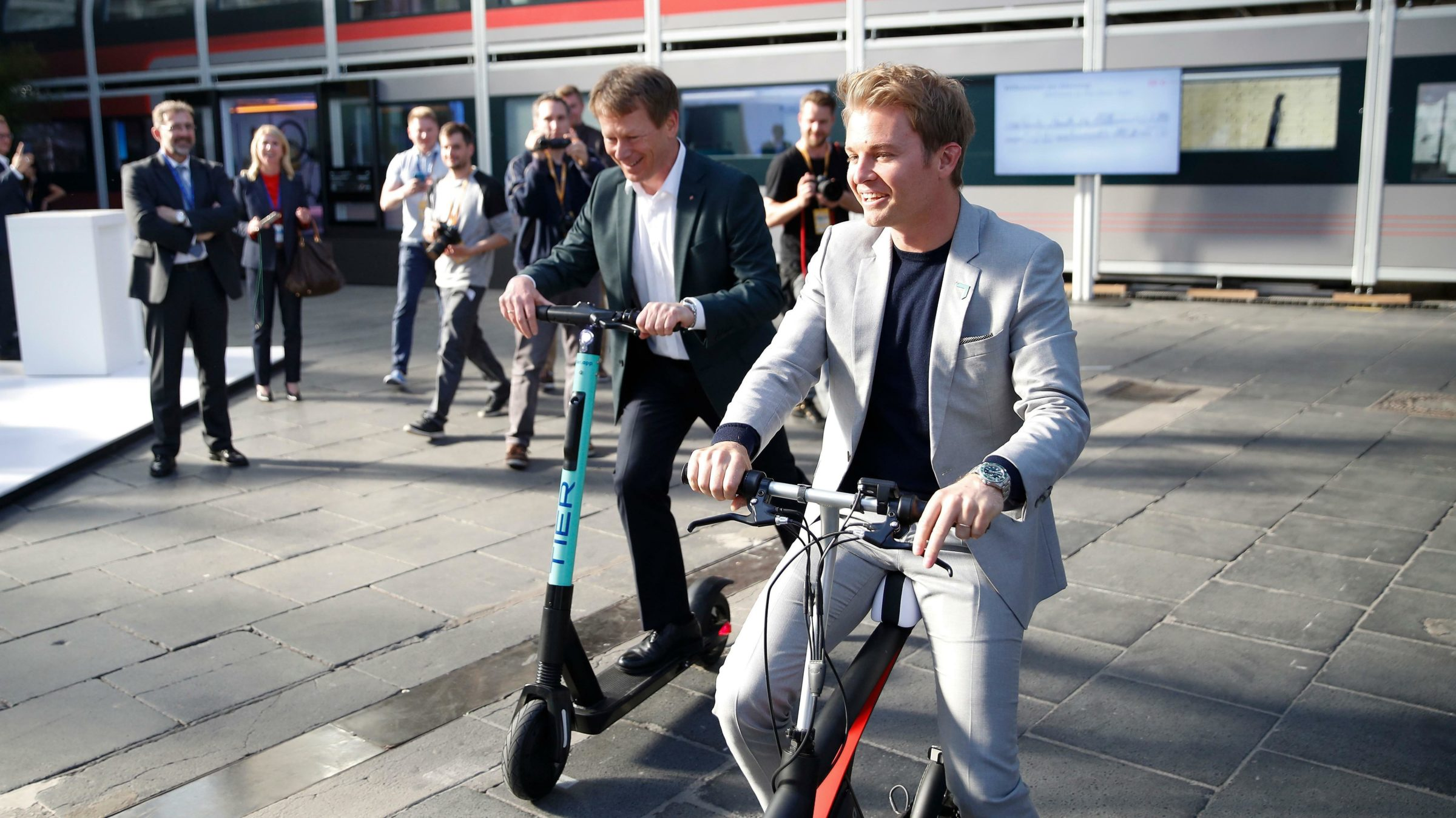 Bahnchef Richard Lutz und Rosberg probieren Elektro-Scooter auf der Greentech Exhibition aus.
