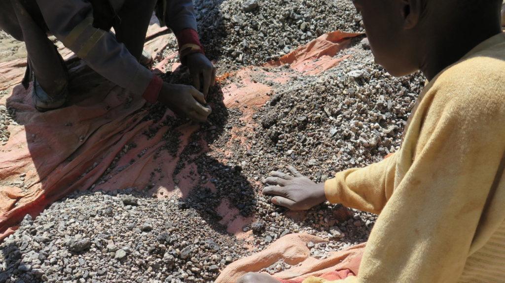 Das am 15.11.2017 zur Verfügung gestellt Handout von Amnesty International zeigt den 13-jährgen Charles, der in der Nähe von Kolwezi (Kongo) mit sein Vater Steine sortiert, die Kobalt enthalten.